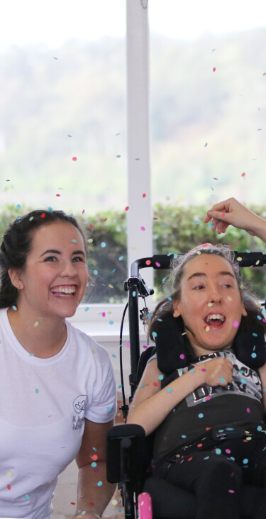 Miss Annabelle, left; student sitting in her wheelchair, middle' and Miss Georgia, right, have confetti thrown over them while they are all giggling enjoying being together